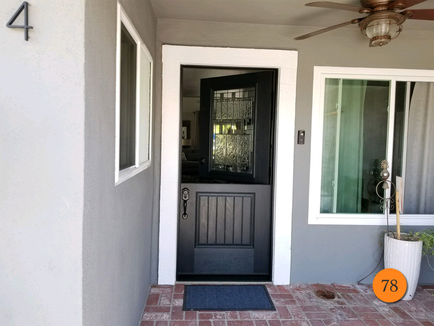 Grey House with dark dutch entry door with an etched glass top half that is swung open