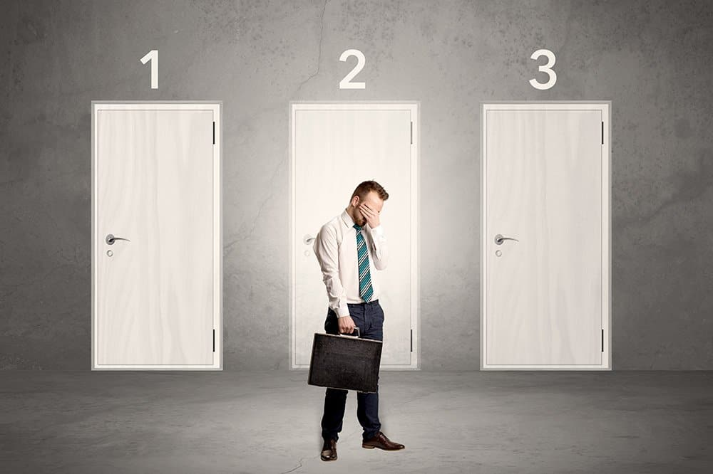 Businessman in grey room with three numbered white door behind his back with decision to make