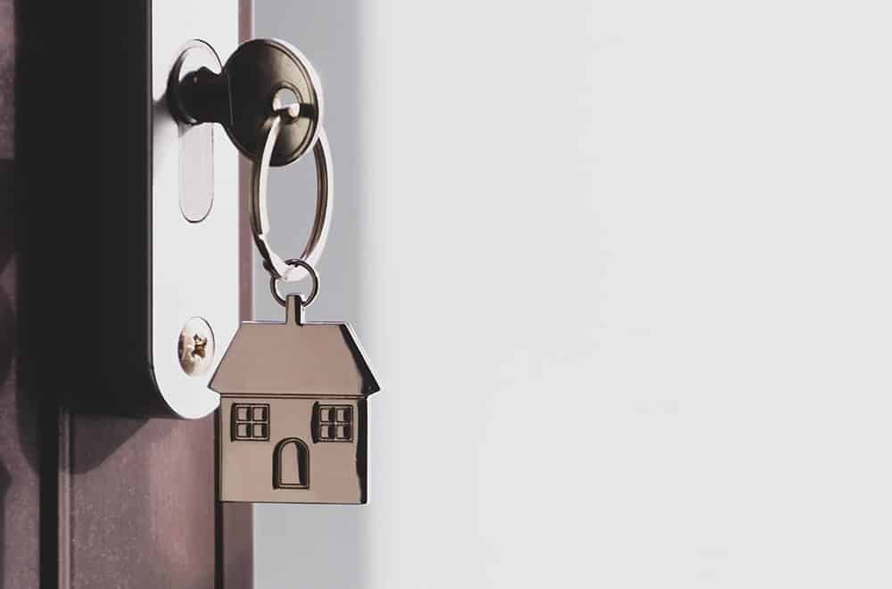 Key with house keyring in the door keyhole