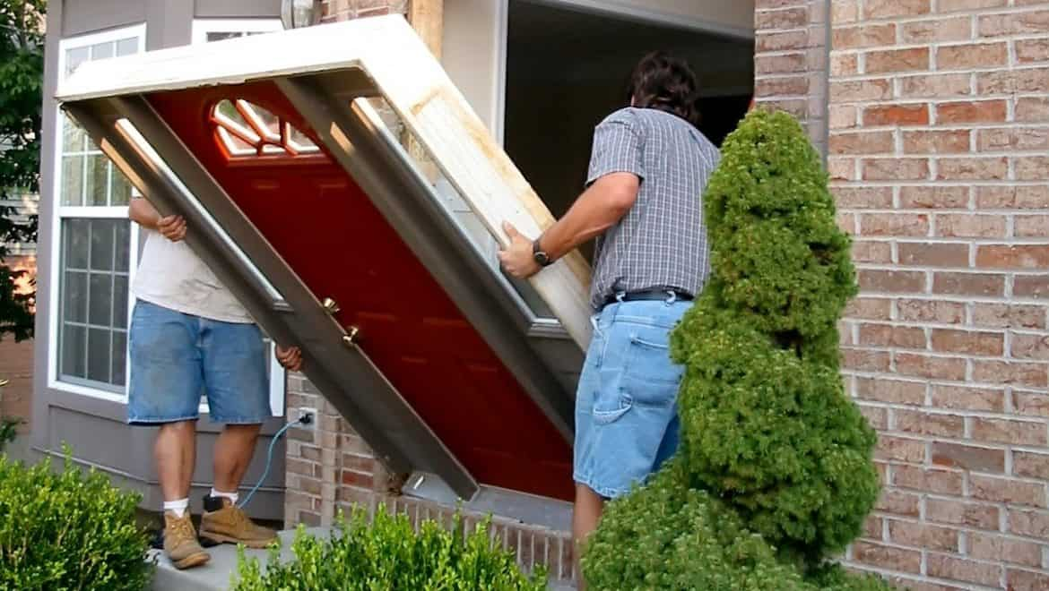 Two men removing a front door from a brick house in the suburbs