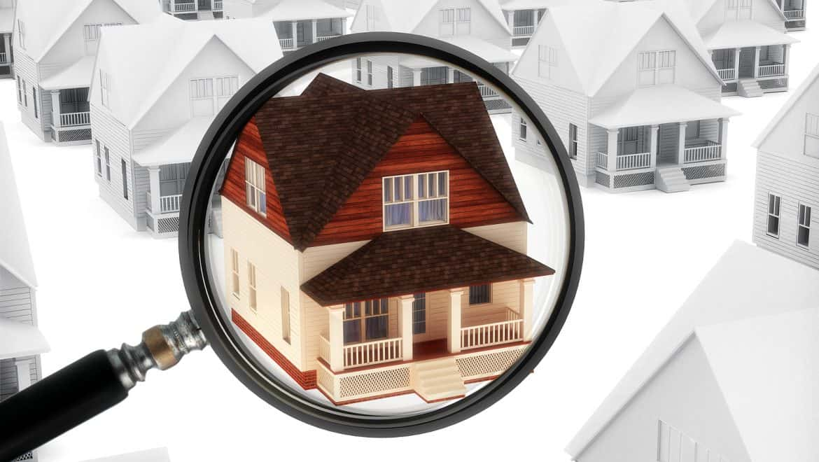 magnifying glass on home over only colored home that stands out