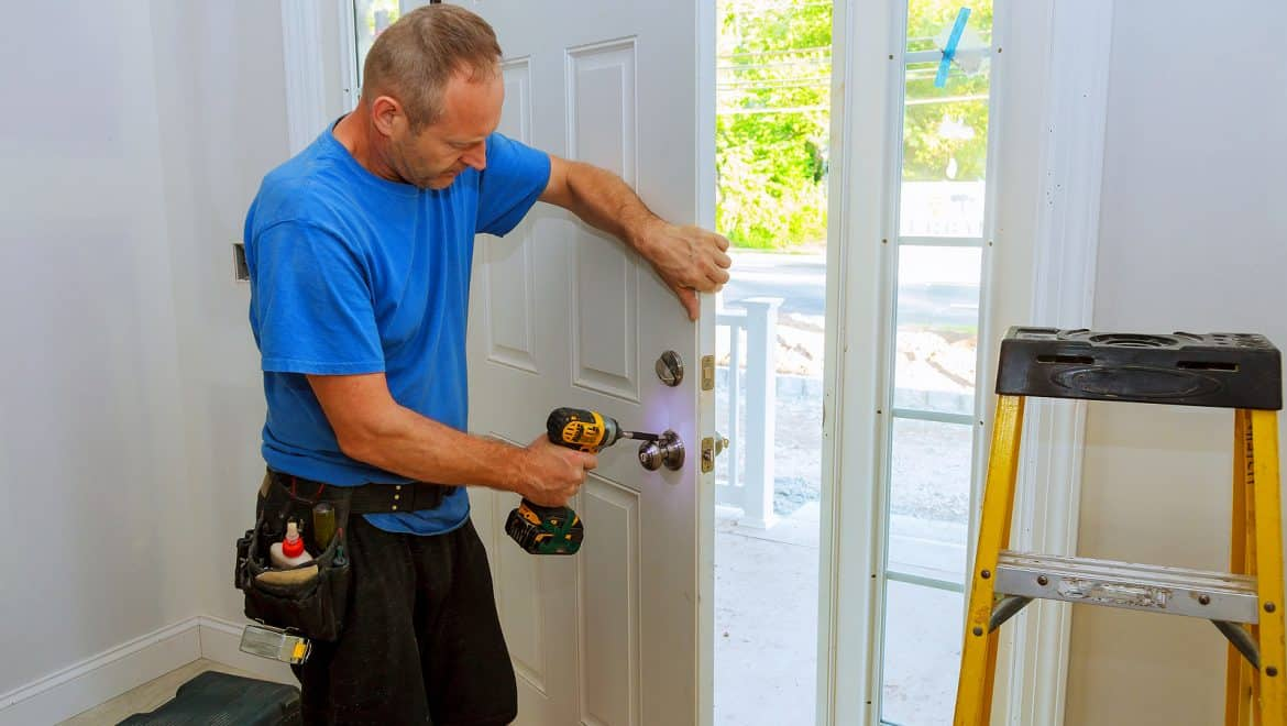 professional finishing up door installation by installing the handle