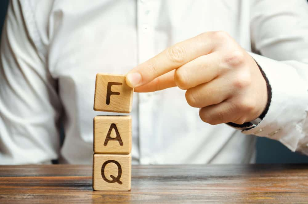 """business man stacking lettered wooden blogs to spell """"FAQ"""""""