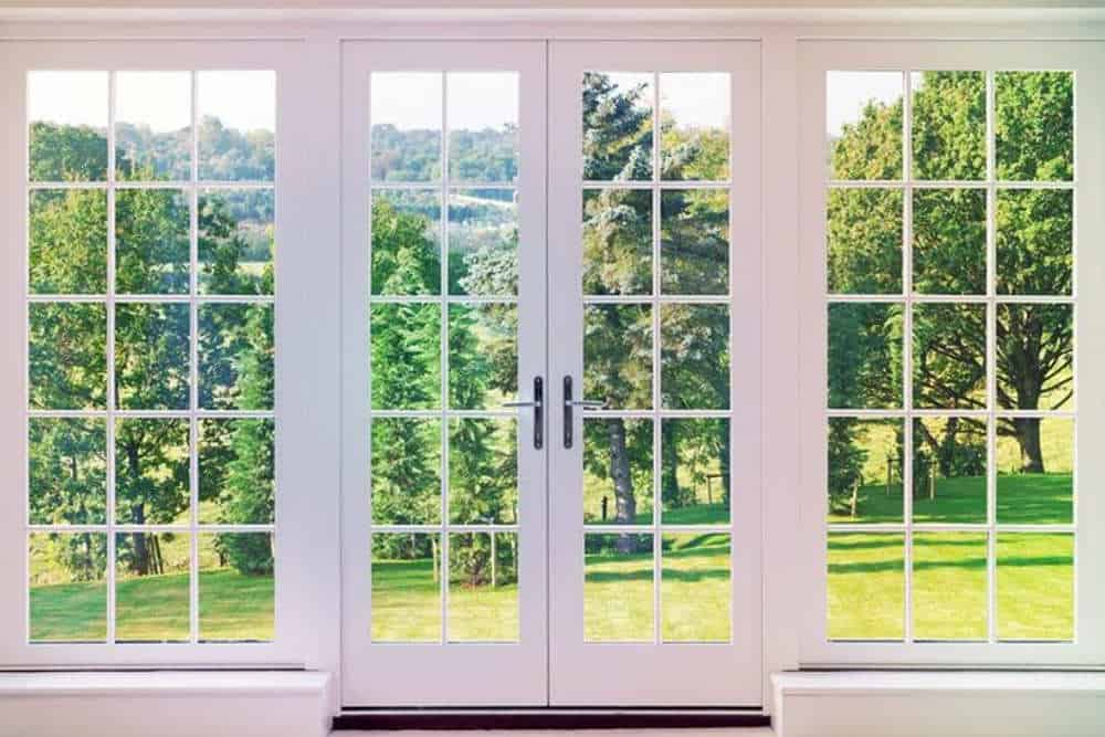Image of beautiful new white french doors with a conventional clear glass grid overlooking a wonderful view of green grass and trees into the horizon.