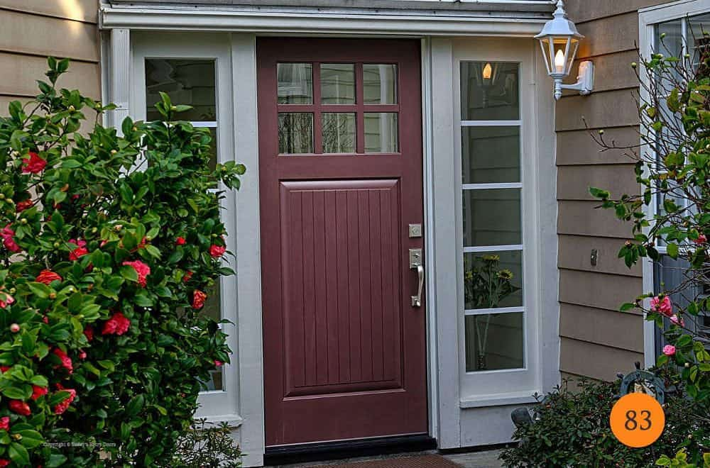 It is an image of a beautiful fiberglass entry door with rich color, sidelights, and lots of green bushes around it. Installed in Orange County, CA by Today's Entry Doors.